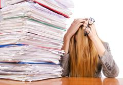 Busy woman with stacks of paper - stock photo
