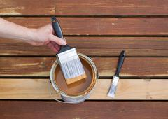 dipping paint brush into a can of wood stain - stock photo