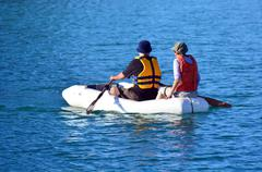 couple rows dinghy boat - stock photo