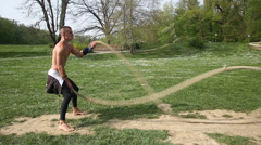 Trained muscular man exercising with ropes - stock footage
