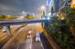 Hong kong city traffic at night in the middle of tall skyscrapers Stock Photos