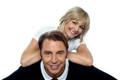 Stock Photo of Beautiful wife leaning over her cheerful husband
