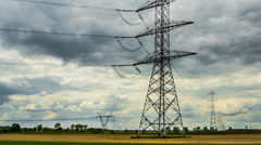 4k or HD Hyper lapse - high-voltage pylons, passing clouds, green field Stock Footage