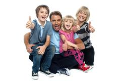 Cheerful thumbs up family - stock photo