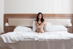 Sad girl in leopard print negligee lying on bed - stock photo