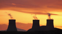Cooling towers of nuclear power plant during golden sunset - stock footage