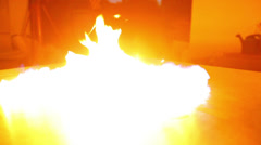 Fire flashes and spreads on reflective surface Stock Footage