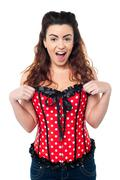 Excited woman adjusting her polka dotted corset top Stock Photos