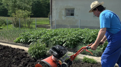 Cultivating garden with smal cultivator in slow motion Stock Footage