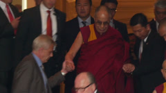 Dalai Lama goes down stairs and is supported by companion Stock Footage