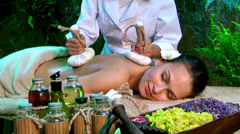 Woman getting thai herbal compress massage in spa. Stock Footage