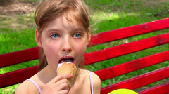 Child eating ice-cream outdoor. - stock footage