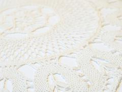 Handmade crocheted doily, closeup, sidelong view - stock photo