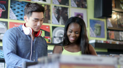 Upward Panning MS A Young Woman and Young Man flick through vintage records - stock footage