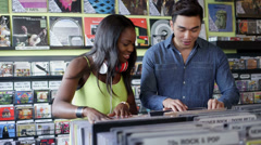 MS A Young Woman and Young Man flick through vintage records together Stock Footage