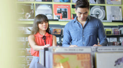 MS A Young Woman and Young Man flick through vintage records together - stock footage