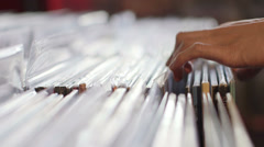 CU A Young Man's fingers flick through a rack of vintage records - stock footage