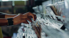 CU A Young Woman's fingers flick through a rack of vintage records Stock Footage