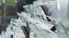 CU A Young Man's fingers flick through a rack of vintage records Stock Footage