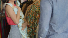 Upward Panning MS A Young Man and a Young Woman browse a vintage clothing store Stock Footage