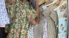 Upward Panning MS A Young Woman chooses between dresses in a vintage clothing Stock Footage
