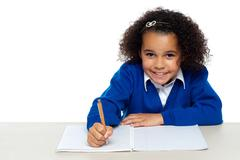 Cute primary kid writing her assignment - stock photo
