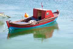 Wooden red row boat in calm water Stock Photos