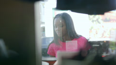 MS A Young Woman peers into the window of a vintage record/clothing store Stock Footage