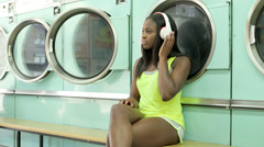 MLS A Young Woman sits waiting in a Launderette Stock Footage