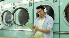 MLS A Young Man sits waiting in a Launderette Stock Footage