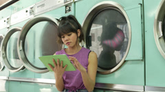 MS A Young Woman sits waiting in a Launderette Stock Footage
