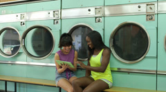 MLS A Two Young Women wait in a Launderette Stock Footage