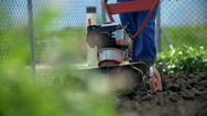 Stock Video Footage of Close up on cultivator mixing soil