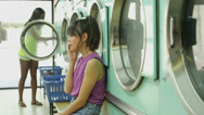 Stock Video Footage of MS Two Young Women use the Launderette