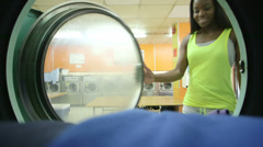 MS A Young Woman retrieves her laundry from the machine Stock Footage
