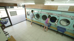 High Angle LS Three Young Adults use the Launderette Stock Footage