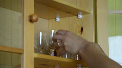 Hands put vintage crystal glasses to wall cabinet Stock Footage