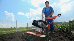 Grower attempts to start the cultivating machine - stock footage