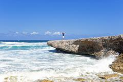 happy guy on the rocks on aruba island in the caribbean - stock photo