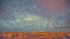 Timelapse night star trails push through storm clouds over golden field Stock Footage