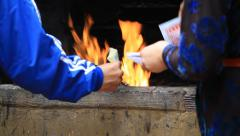 Man and woman burning fake paper money at the incinerator Stock Footage