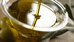 Olive oil dripping on bowl close up - camera moving downwards - stock footage