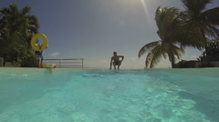 Man jumping into swimming-pool Stock Footage