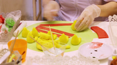 Gloved hands creating of color sweet figures in confectionary Stock Footage