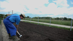 Man uses the shovel to manually turn around some of the soil Stock Footage