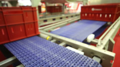 Red plastic boxes move on two blue industrial conveyors Stock Footage
