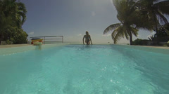 Woman jumping in swimming pool Stock Footage