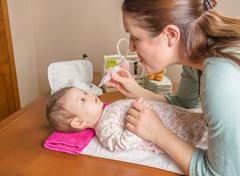 Mother cleaning mucus of baby with nasal aspirator Stock Photos