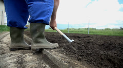 Close shot of farmer tunring around the soil to make it fresh on the surfacace Stock Footage