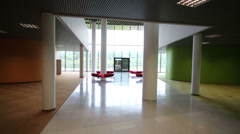 Empty hall with red soft unusual benches in modern building Stock Footage